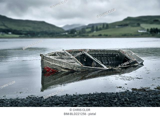 Dilapidated boat in rural lake