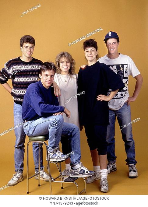 Studio portrait of a group of five happy teenagers in casual clothes