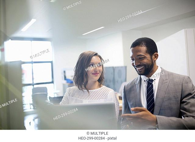 Smiling businessman and businesswoman using laptop in office