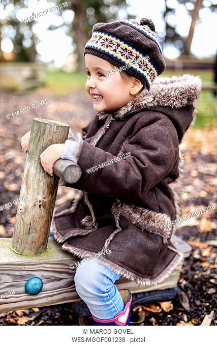 Happy little girl on a playground in autumn