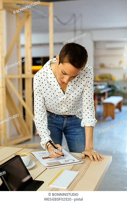 Woman working on draft at desk in office