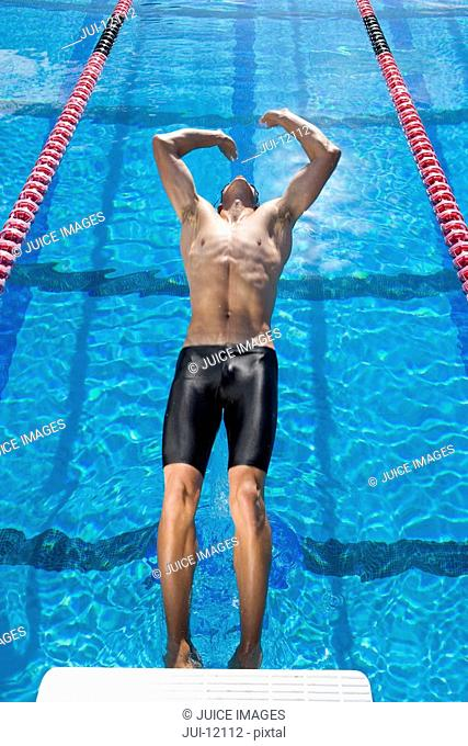 Male swimmer diving into swimming pool backwards, elevated view