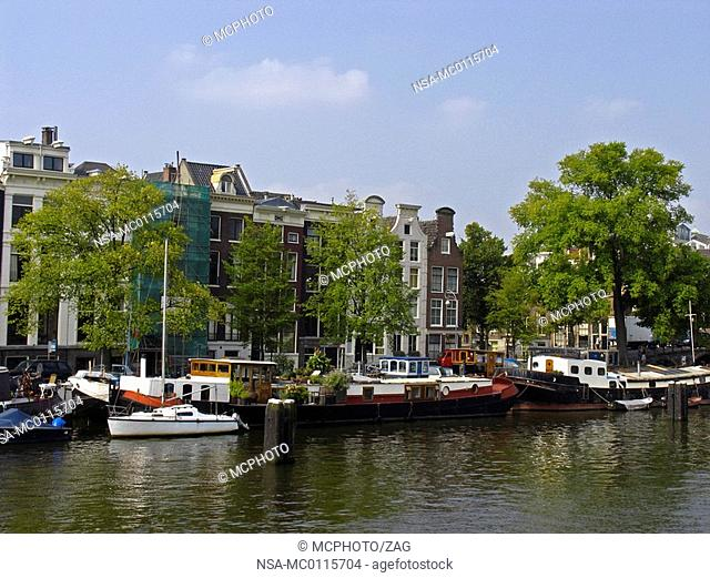 the river Amstel with old canal houses and houseboats, Amsterdam, Holland, The Netherlands