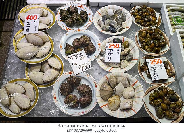 Dishes with fresh diversity of sea shells on ice and price tags at the Omicho Market
