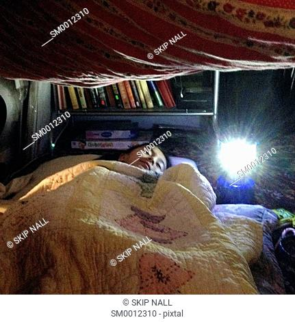 Little girl sleeping in a child's tent made in her home with blankets