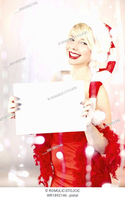 Young woman in Santa Claus costume holding empty list of wishes