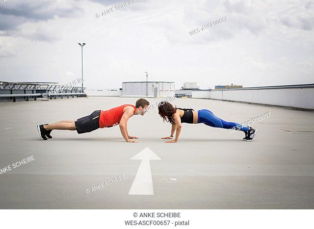 Man and woman doing push ups outdoor