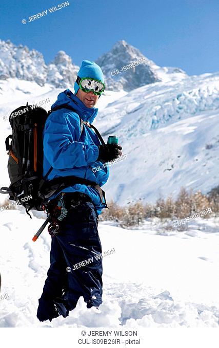Portrait of male snowboarder wearing ski goggles in deep snow, Trient, Swiss Alps, Switzerland