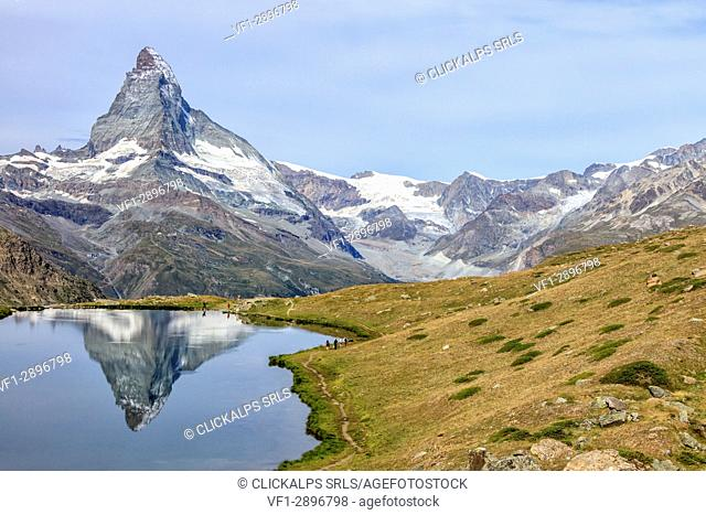 Hikers on the trail to the Matterhorn reflected in Lake Stellisee Zermatt Pennine Alps Canton of Valais Switzerland Europe