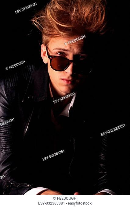 Portrait of a handsome young fashion man looking over his suglasses