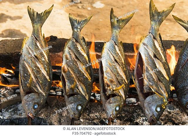 Fish grilling over fire