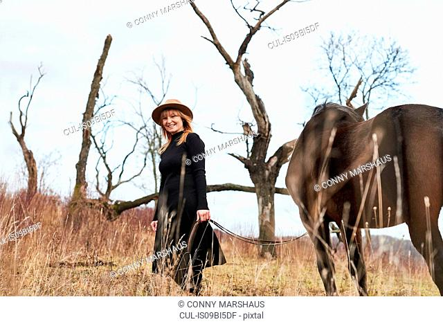 Portrait of woman with horse, looking at camera smiling