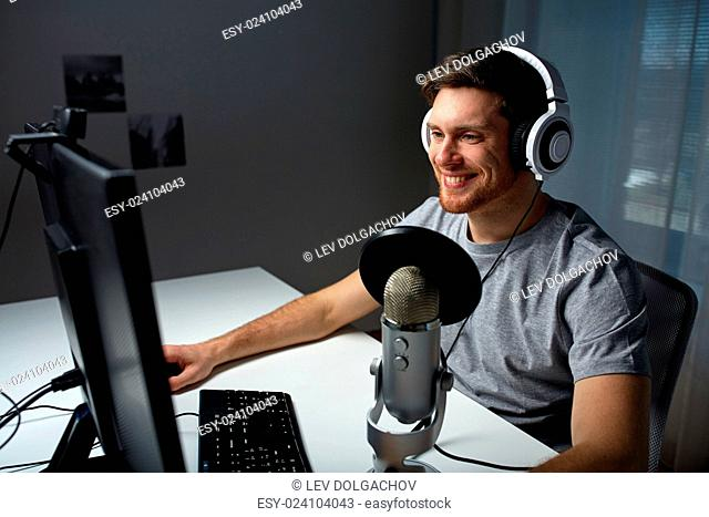 technology, gaming, entertainment, let's play and people concept - happy young man in headset with pc computer playing game at home and streaming...