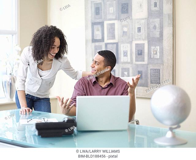 African businessman and businesswoman talking in office