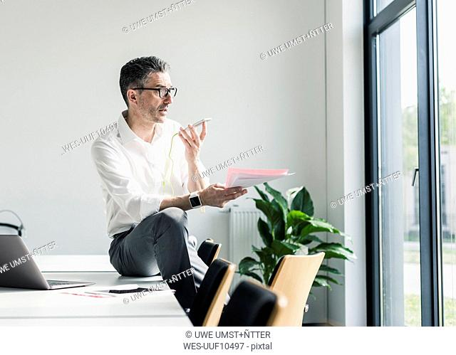 Businessman using cell phone in a conference room
