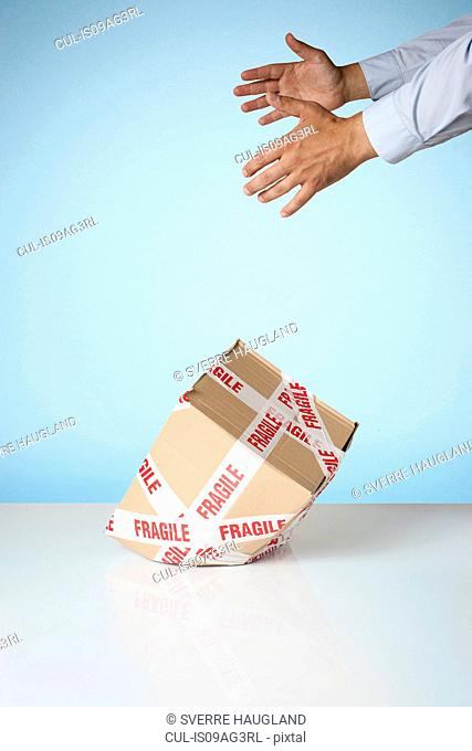Studio shot of hands dropping cardboard box marked fragile