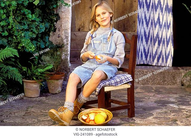 portrait, full-figure, girl with blond plaits, 10 years, wearing pullover and jeans bermudas with flap and boots sits on a chair pealing tangerines  - GERMANY