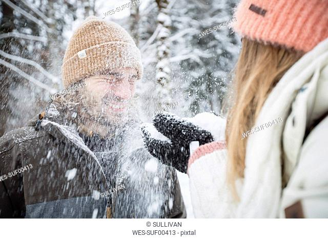 Happy couple having fun with snow in winter landscape