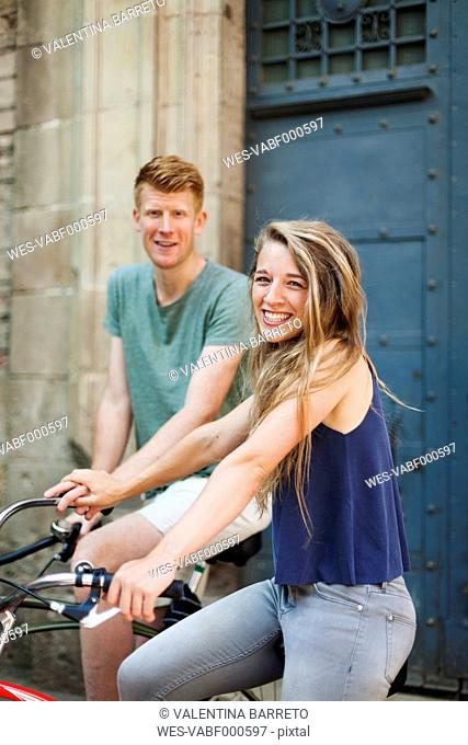 Portrait of laughing woman with bicycle holding hand with her boyfriend in the background