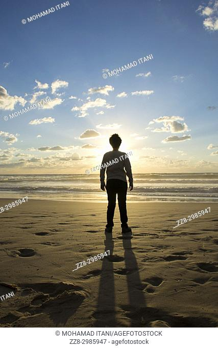 Silhouetted young boy standing on the beach at sunset