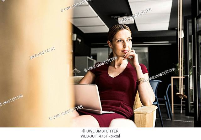 Businesswoman in office lounge wearing burgundy dress using laptop