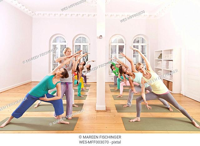 Group of people in yoga studio holding triangle pose