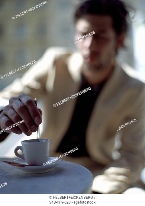 Mid adult man in a white sack coat stirring his espresso with a silver spoon, selective focus