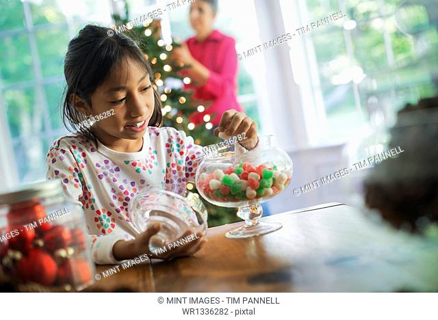 A young girl with a large glass jar of organic holiday gum drops. Decorations for Christmas