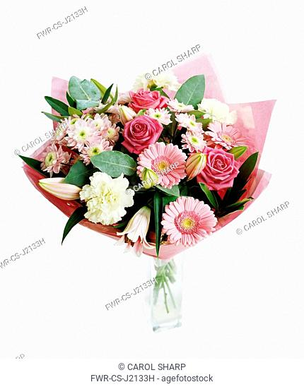 Carnation, white Dianthus with pinnk chrysathemems, gerberas, lilies and roses, Floral arrangement as a bouquet with pink tissue in a glass vase