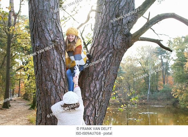 Teenage girl by river helping frind to climb tree