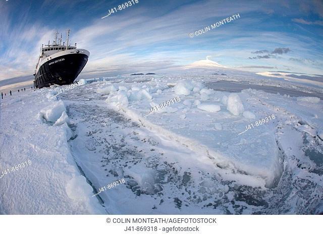 Marina Svetaeva, Ice-strengthened Russian cruise ship ( Aurora Expeditions) in McMurdo Sound sea ice - volcano Mt Erebus behind- volcano Mt Erebus behind