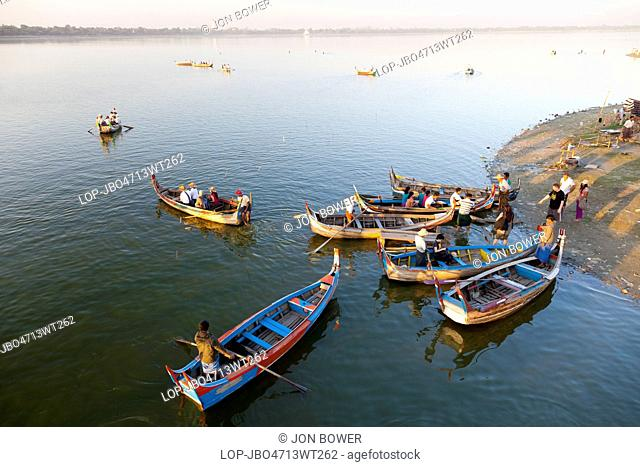 Myanmar, Mandalay, Lake Taungthaman. Tourist pleasure boats plying their trade by U Bein Teak Bridge across Taungthaman Lake in Myanmar