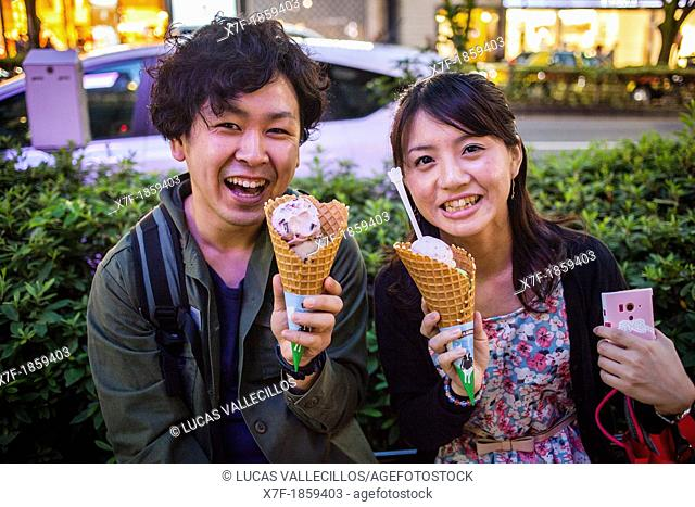 Couple eating Ben & Jerry's ice cream, in Omotesando street  Tokyo  Japan