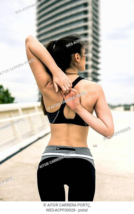 Sportive woman stretching shoulder and arm, rear view