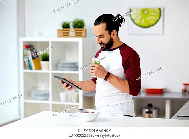 vegetarian food, healthy eating, people, technology and diet concept - man having muesli with vegetable smoothie for breakfast and looking to tablet pc computer...