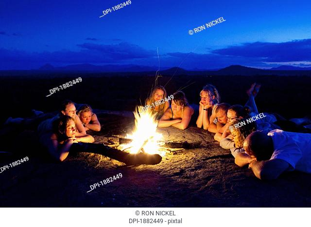 A Group Of People Laying By A Campfire, Manica, Mozambique, Africa