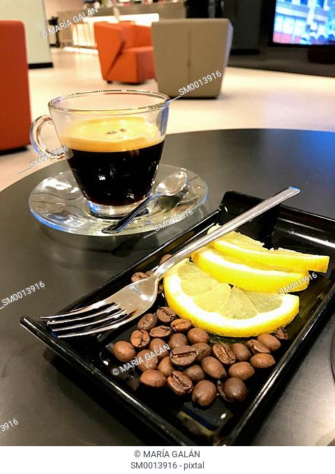 Cup of carajillo, coffee and brandy, with coffee beans and sliced lemon in a cafe