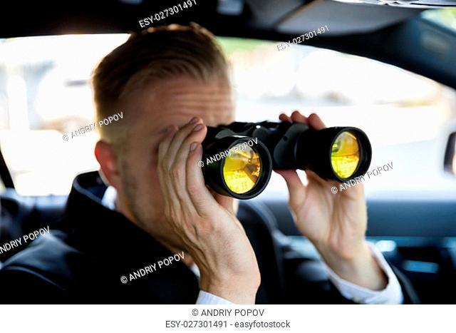 Private Detective Sitting In Car Looking Through Binocular