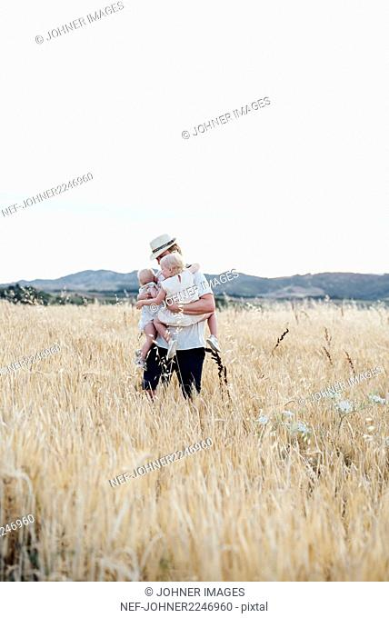 Father carrying two babies in field