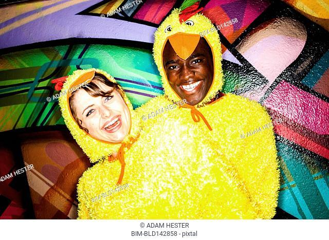 Couple in chicken costumes smiling near graffiti wall