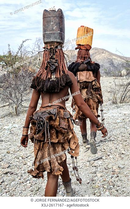 Himba women carrying plastic containers full of water on their heads