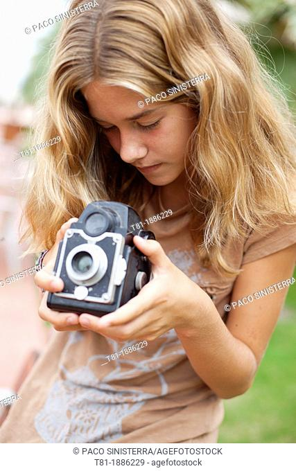 Spain, teenage girl looking at vintage camera