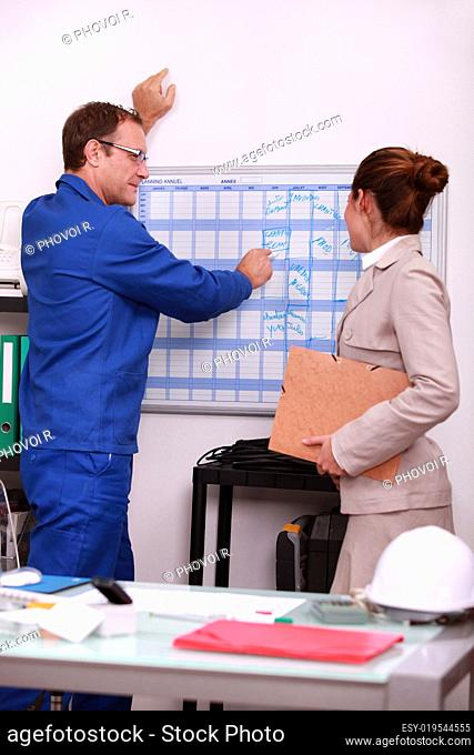Construction foreman arranging a meeting with an engineer