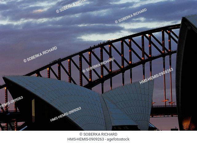 Australia, New South Wales, Sydney, roof of the Opera House designed by architect Jon Urtzon listed as World Heritage by UNESCO before the Harbour Bridge at...