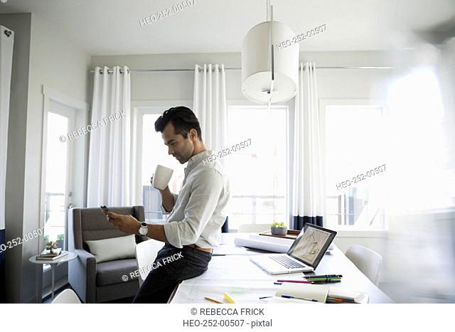 Architect drinking coffee and texting in dining room