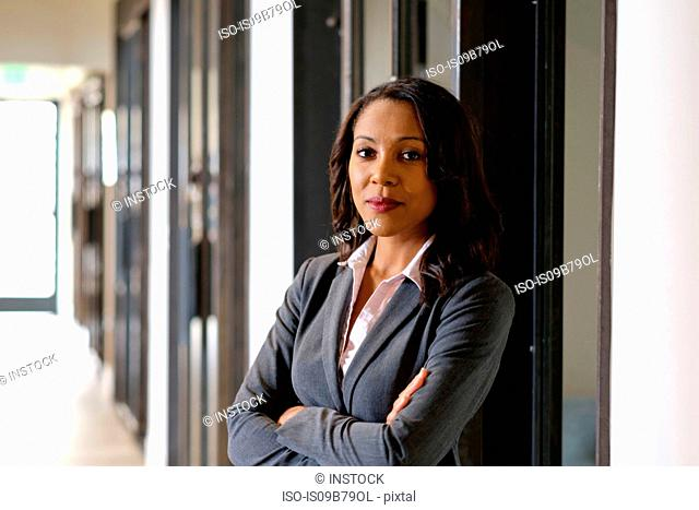 Portrait of businesswoman in office hallway, arms folded, serious expression