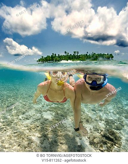 couple swimming in front of remote tropical island
