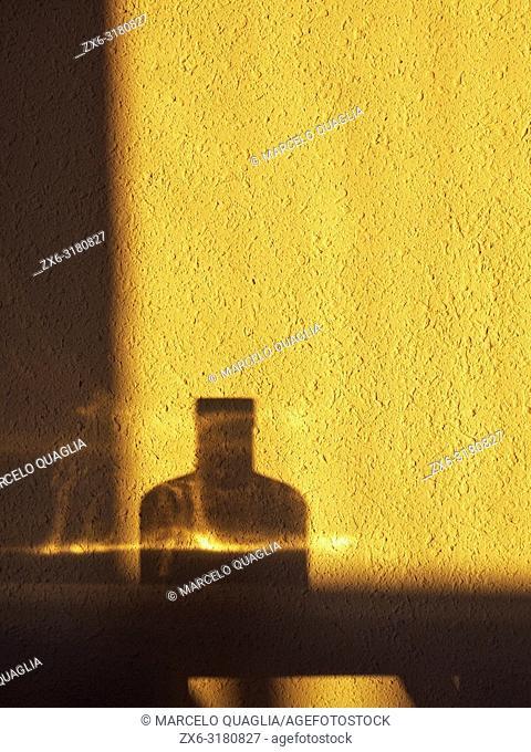 Bottle reflection over wall under sun rising light. Barcelona province, Catalonia, Spain