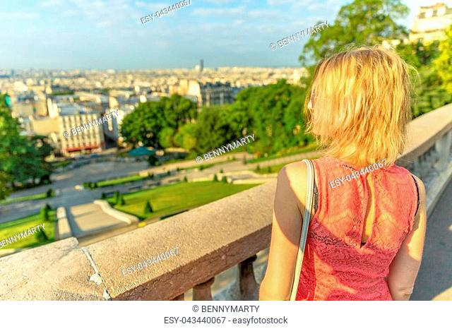 Close up of elegant caucasian woman looking skyline of Paris from Sacred Heart viewpoint. Parisian views from terrace of Sacre Coeur Cathedral