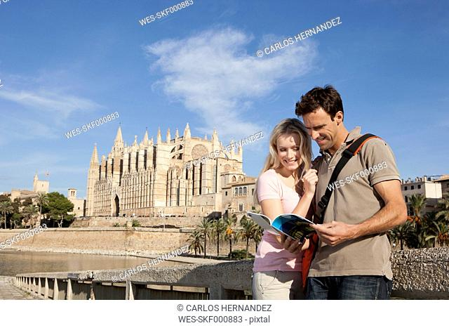 Spain, Mallorca, Palma, Couple looking in guide book with St Maria Cathedral in background, smiling